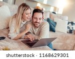 smiling couple using laptop at... | Shutterstock . vector #1168629301