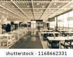 Stock photo vintage tone blurred large open space cafeteria canteen food court at shopping mall or corporate 1168662331