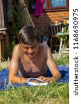 Teenage boy reading a book while sunbathing in a garden smiling - stock photo
