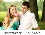 Young woman flirting with a man, eating candy - stock photo