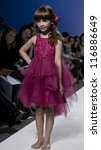 NEW YORK - OCTOBER 20: Girl walks runway for petite Parade show collection by Mischka Aoki during kids fashion week NYC sponsored by Vogue Bambini at Industria Superstudio on October 20, 2012 in NYC - stock photo