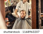 barber put on apron around... | Shutterstock . vector #1168963207