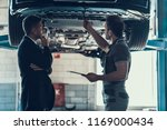 Small photo of Auto Mechanic Showing Client Car Problem. Handsome Buisiness Man in Black Suit Listening Cause of Breakage. Automobile Master in Uniform Explainig in Garage. Repair Service Concept.