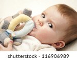 Baby Girl is looking at the camera with her toy - stock photo
