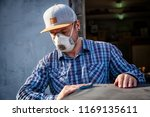 Experienced carpenter in work clothes and small business owner working in woodwork workshop,  using sandpaper for polishing wooden  at worktable in workshop   - stock photo