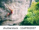 a man in helmet climbs the rock.... | Shutterstock . vector #1169502037