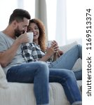loving couple sitting on a sofa ... | Shutterstock . vector #1169513374