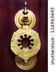 Vintage image of ancient door knocker on a wooden door. - stock photo