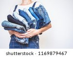 the girl holds a stack of jeans ... | Shutterstock . vector #1169879467