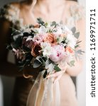 the bride is holding a wedding... | Shutterstock . vector #1169971711