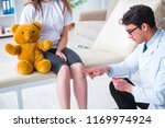 doctor checking up young girls... | Shutterstock . vector #1169974924