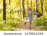 Small photo of Autumn, nature, people concept - young woman in a blue coat dancing in the park on a background of trees with a cup of coffee and suitcase