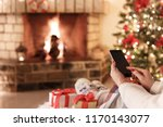 Woman sitting by fireplace and christmas tree using smartphone holiday cozy concept - stock photo