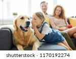 Stock photo little girl whispering something to her pet while relaxing on sofa on background of young couple 1170192274