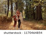 Stock photo young beautiful girl playing with a dog in the park autumn sunny day 1170464854
