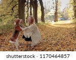 Stock photo young beautiful girl playing with a dog in the park autumn sunny day 1170464857