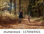 Stock photo young beautiful girl playing with a dog in the park autumn sunny day 1170465421