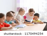 female teacher helping children ... | Shutterstock . vector #1170494254