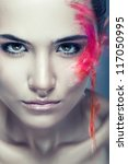 cute woman with flying coloured powder on face - stock photo