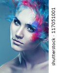 woman with flying coloured powder above eye - stock photo