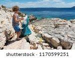 little boy cleaning up beach... | Shutterstock . vector #1170599251