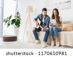 smiling couple tuning acoustic... | Shutterstock . vector #1170610981