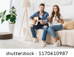young smiling couple sitting on ... | Shutterstock . vector #1170610987