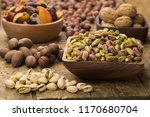 pistachios nuts peeled in bowl... | Shutterstock . vector #1170680704