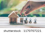 house placed on coins men's... | Shutterstock . vector #1170707221