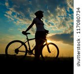 Small photo of Biker-girl at the sunset on the meadow
