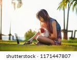 Small photo of sad and lovelorn heart broken woman stay sitting with puppy on the field grass, listening music on line while see the last love in note book, lonely morning occasion