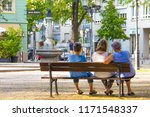 Small photo of Unidentified elderly women are sitting on a wooden bench in the middle of the city center of a German city and chat about different things and spend time together