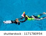 Small photo of Diving people underwater in sea with corals and fish around, scuba diver open waters beginner course with professional instructor and young kid first time exploring swimming with dolphins with motor
