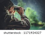 Caucasian Hunter in Masking Camouflage Uniform with Binoculars. Hunter Spotting Game. Poacher or Soldier Clothing. - stock photo