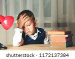 tired schoolboy sits at table... | Shutterstock . vector #1172137384