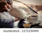 woman pours tea into a cup.... | Shutterstock . vector #1172150404