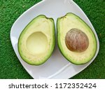 two slices avocado with core on ... | Shutterstock . vector #1172352424