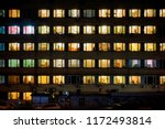 Frontal view of the night facade of building with a lot of windows with yellow green white light. life in every window.