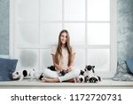 Stock photo a beautiful young girl sits on the windowsill of a white window and holds a lot of small puppy of a 1172720731