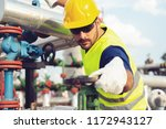 worker closes the valve on the... | Shutterstock . vector #1172943127