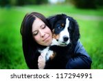 Stock photo beautiful dog portrait bernese mountain puppy berner sennenhund with a beautiful girl on the 117294991