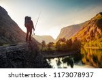 hiker stands on the rock with... | Shutterstock . vector #1173078937