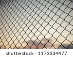 sky through wire mesh fence.... | Shutterstock . vector #1173334477