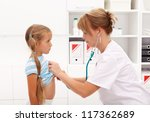 Little girl at the doctor being examined with stethoscope - stock photo