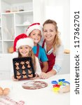 Kids wearing santa hats making christmas cookies with their mother - stock photo