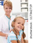 Little girl smiling at the doctor - back after recovery for a checkup - stock photo