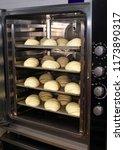 raw bread on a baking sheet... | Shutterstock . vector #1173890317