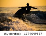 A Silhouetted Surfer Carves On...