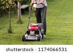 lawnmower in action at backyard | Shutterstock . vector #1174066531