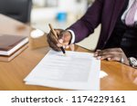 Small photo of African american man signing contract, black man hand putting signature on official document, biracial clients customers couple make purchase or sign prenuptial agreement concept. clouse up